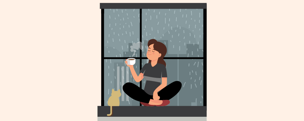 A person drinking coffee near the window beside her pet cat