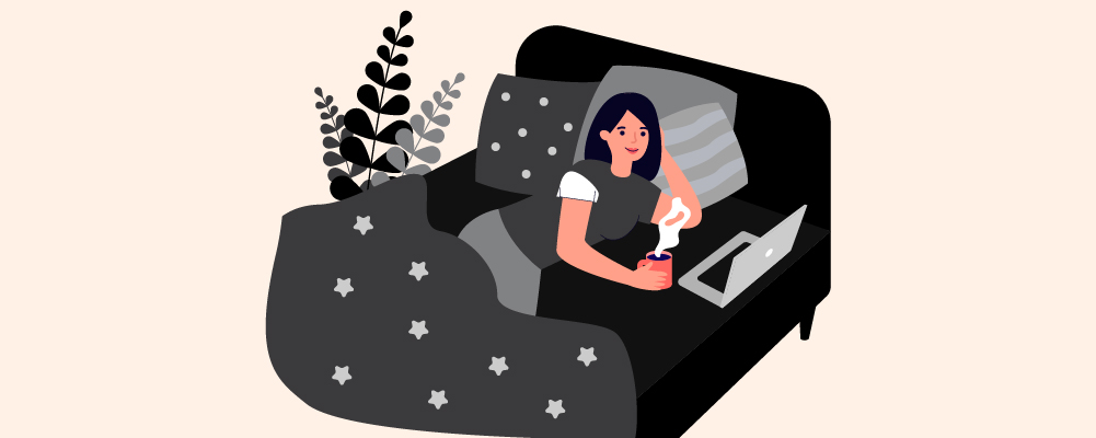 A woman on a bed watching something on a laptop while drinking coffee